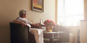 Senior woman sitting alone: lonliness can harm seniors